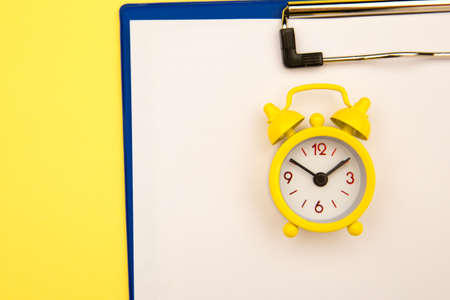Yellow clock on yellow background, empty space for text