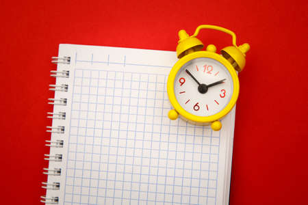 Yellow alarm clock on notebook on red background, empty space for text 版權商用圖片