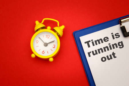Time is Running Out - phrase on paper with yellow alarm clock aside on red background 版權商用圖片 - 164917832