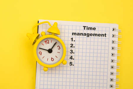 Time management concept. Open small notebook with to-do list and yellow alarm clock aside.