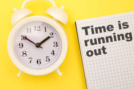 Time is Running Out - phrase on notebook with white alarm clock aside on yellow background