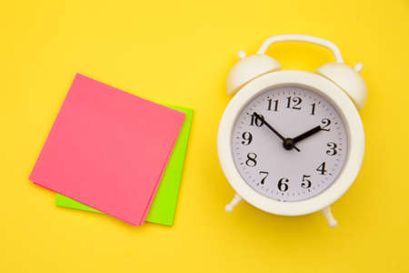 White alarm clock and colorful sticky notes on a yellow background. The concept of working time. Workplace