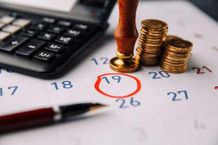 Coins with the calculator on calendar close-up 版權商用圖片