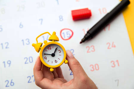 Young woman hand holding yellow clock. Calendar in background. Positive result. It is a time for baby.Gynecology concept
