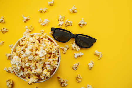 Bowl with popcorn and 3d glasses on a yellow background. Top view