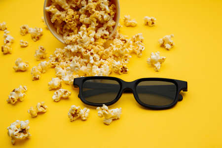 Popcorn in a bowl and 3d glasses on yellow background. Entetainement concept