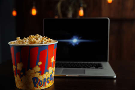 Popcorn in bowl and laptop playing movie. Film, fastfood. Entertainment concept