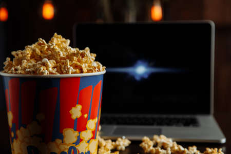 Have a good evening watching a movie on a laptop with popcorn. Fast food. Corn
