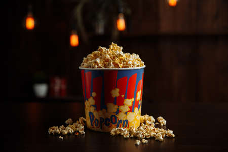 Popcorn in a bright box isolated on wooden background. Closeup view 版權商用圖片