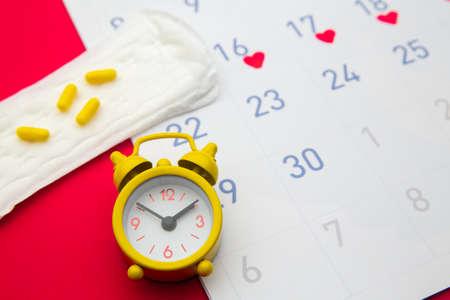 Menstrual calendar with pads, alarm clock, hormonal contraceptive pills. Menstruation period concept. Pain reliever for menstrual pain