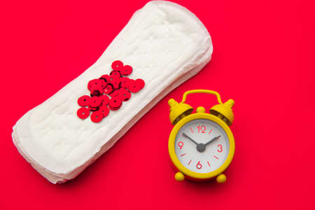 Sanitary pads and alarm clock on red background. Females menstrual cycle concept