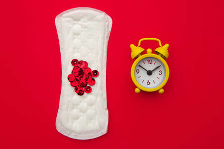 Medical conception photo. Daily pad and yellow clock. Woman critical days, gynecological menstruation cycle. Menstruation sanitary woman hygiene