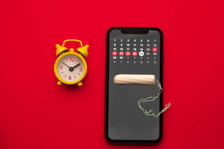 Mobile application to track your menstrual cycle and for marks. PMS and the critical days concept. Cotton tampon and yellow alarm clock on the red background