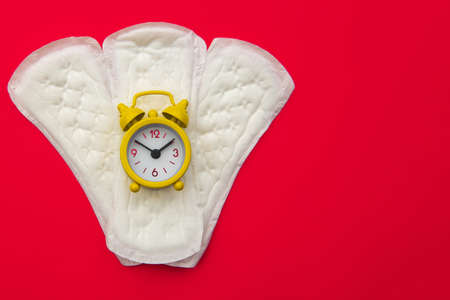 Daily pads and yellow alarm clock on red background. Females menstrual cycle concept