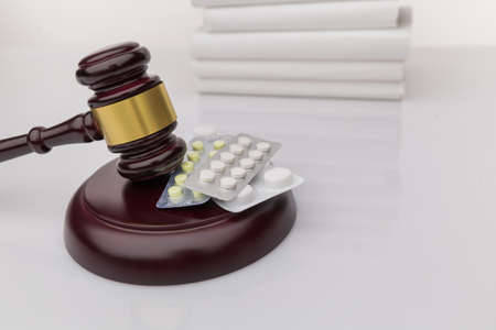 Drugs and law. Judge gavel and colorful pills on a wooden desk, dark background, closeup view