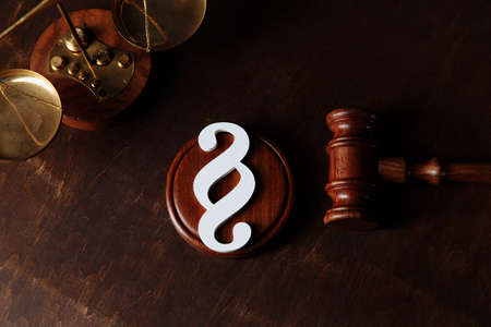 Paragraph symbol and gavel in courtroom. Law and justice concept