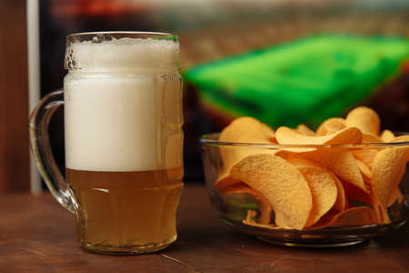 Beer glass and chips in front of tv. Football at home Standard-Bild