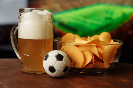 Beer glass, soccer ball and chips in front of screen. Football fans concept