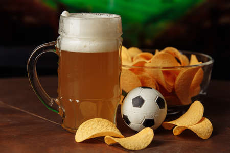 Glass of cold beer, soccer ball and snack close-up Standard-Bild