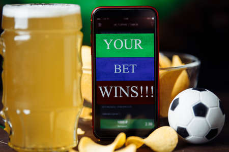 Glass of beer and mobile app for online betting. Football match online broadcast on laptop screen on the background