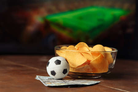 Soccer ball with potato chips in a bowl on football background