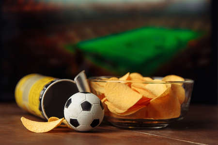 Soccer ball with potato chips in a bowl and screen with football game background