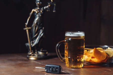 Drunk driving concept. Lady of justice, glass of beer and car key
