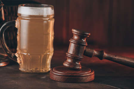 Glass of beer and judge gavel as a symbol of law on a wooden table close-up Standard-Bild