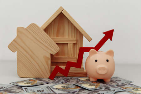Piggy bank with arrow up and wooden house models on dollar banknotes, Saving or loan for buy house or real estate owner concept.