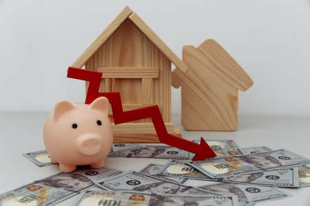 Pink piggy bank with arrow down and wooden house models on dollar banknotes, Saving or loan for buy house or real estate owner concept Standard-Bild