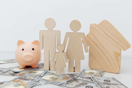Piggy bank and figures of family with a wooden house on dollar banknotes