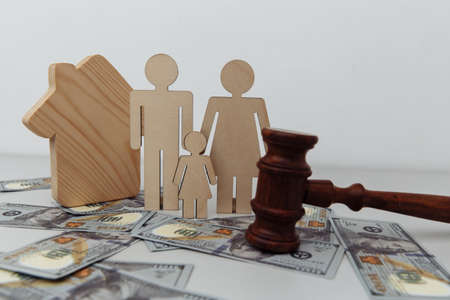 Family figure with judge gavel and house on dollar banknotes. Family protection or law concept