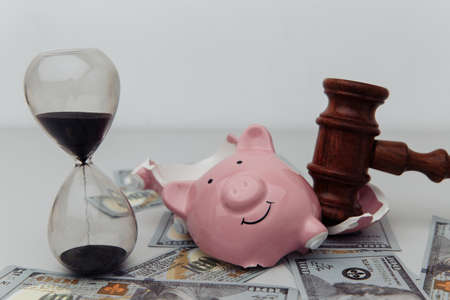 Broken piggy bank, hourglass and judge gavel. Bankruptcy or crisis concept