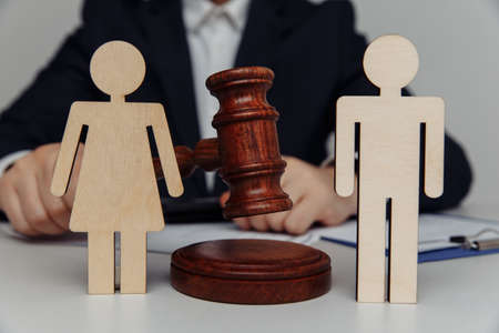 Lawyer or counselor holds gavel behind of figures of young family, divorce and law concept Standard-Bild