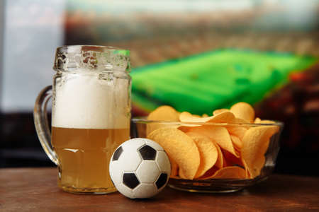 Beer glass, soccer ball and chips in front of tv. Football fans concept