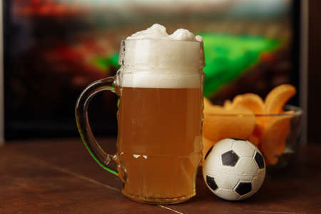 Glass with beer and snack in front of screen with football game. Soccer fans