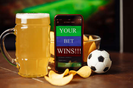 Glass of beer and mobile app for betting. Football match online broadcast on laptop screen on the background