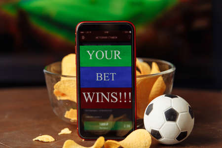 Mobile app for online betting and soccer ball with potato chips. Football match online broadcast on laptop screen on the background Standard-Bild