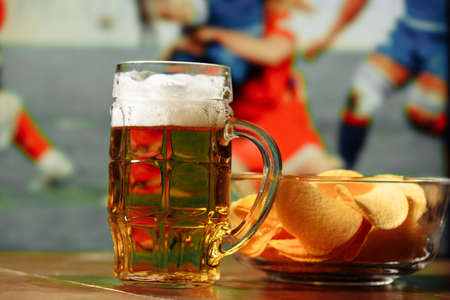Beer with snack on wooden table against football field background. Sport and entertainment concept Standard-Bild