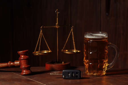 Glass of beer, car keys and wooden judge gavel in a notary office. Alcohol and law concept