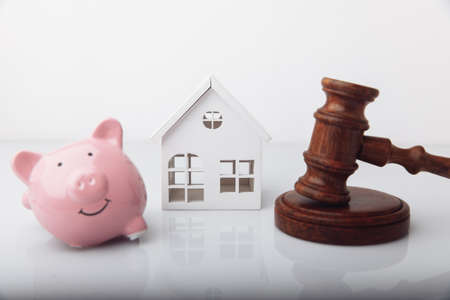 Gavel, broken piggy bank and house model isolated on white. Auction concept