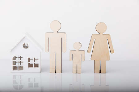 Wooden model of house and family isolated on white background Фото со стока