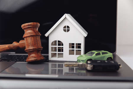 Wooden judge gavel with house and car with key. Auction and bidding concept