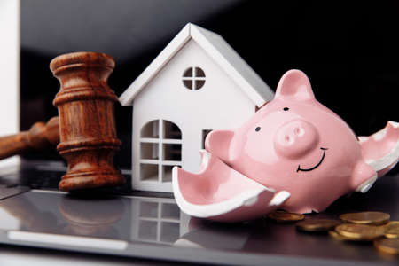 Wooden gavel, broken piggy bank and white house. Real estate auction concept