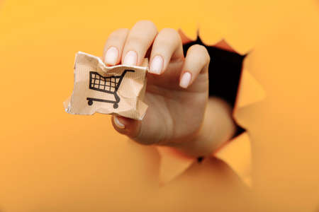 Hand with a small broken delivery box through a yellow paper hole. Delivery accident