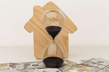 Wooden house and clock on dollar banknotes close-up. Buying or selling real estate Фото со стока