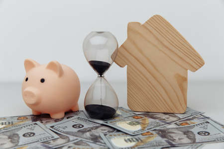 Wooden house, piggy bank and clock on dollar banknotes. Investment, savings and real estate