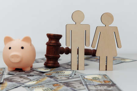 Wooden family figures, gavel and pink piggy bank on dollar banknotes, savings concept