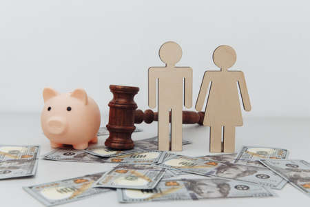 Wooden family figures, gavel and pink piggy bank, savings and divorce concept