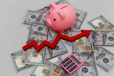 Piggy bank and arrow up on dollar banknotes